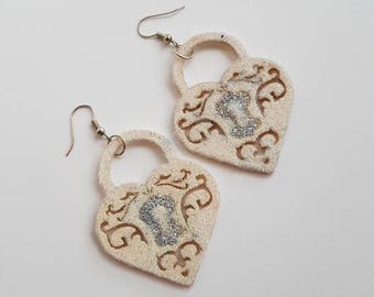 Sparkly heart padlock earrings made from wood and covered in glitter.