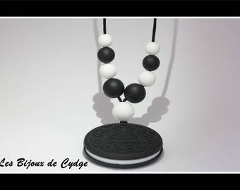 Black and white color nursing necklace and a biscuit