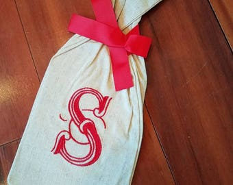 Burlap wine bottle bag/holder with single initial and red ribbon tie.