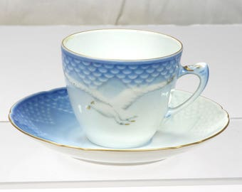 Collectible Royal Copenhagen Porcelain 463 demitasse in blue with seagull motif and gold edging.