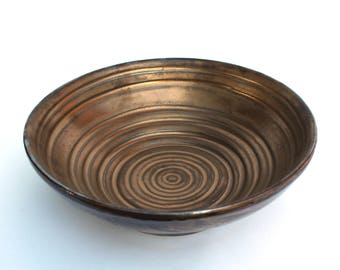 Metallic gold bowl with white frosting on the outside