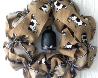 "16"" Burlap wreath with cow print, black and white checkered ribbon, bows, and a hanging cow bell, burlap natural farmhouse style"
