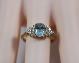 Gold Tone 6mm Oval Cut Light Blue Topaz with Rhinestone Accents Ring Size 8