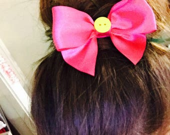 Pink bow with a yellow button