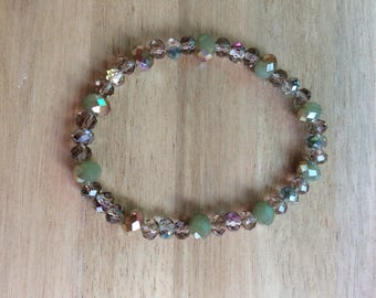 Elasticated bracelet made with Swarovski crystal beads in shades of green and gold.