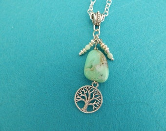 Natural green stone pendant, accented by small beads and a tree of life