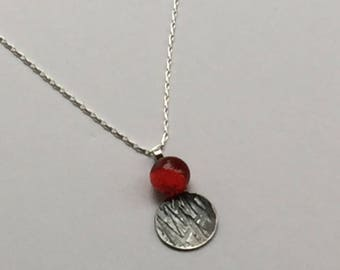Oxidised Sterling Silver pendant with bright red glass bead.