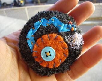 Broche en laine bouillie cousue main dans les tons gris, orange et bleu. Broche ronde.  Pièce unique. Made in France.