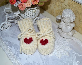 Booties (small socks)  for a child, a newborn knitting with a pattern of the heart