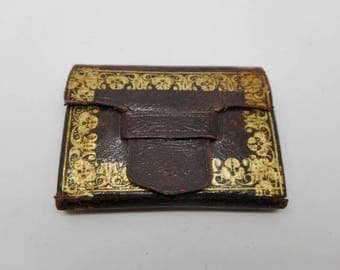 A gold tooled leather needle case.