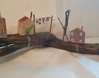 Reclaimed wooden cottages with toadstools, washing line and tree.