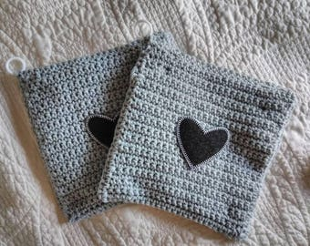 "Handmade pot holders made with 100% USA grown cotton. Black denim heart applique on gray background. Generous 8"" x 8"" size."