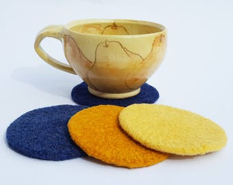 4 felted wool coasters: yellow, gold, blue, navy