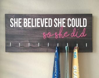 "Race Medal Holder - ""She believed she could SO SHE DID"" white and pink with gray woodgrain background"