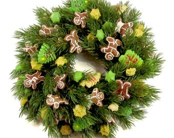 "Christmas wreath or centerpiece. 10 inch artificial wreath with durable, handmade, salt-dough ""cookies"". Features gingerbread men."