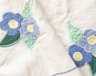 A vintage linen table cloth with appliqué linen flowers and ladder stitch squares
