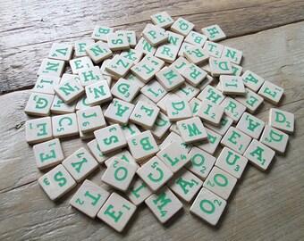 Vintage wooden scrabble tiles or game pieces, set of 100, matte green letters.
