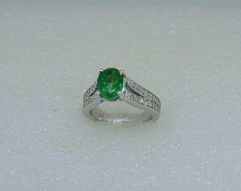 Emerald and diamond ring in 18 carat white gold. 8mmsx6mms Emerald and 36 diamonds make up this outstanding modern ring