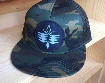 UNS Tribal Patch, on a Camouflage baseball cap.