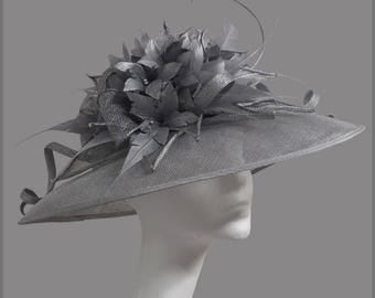 Stunning silver ladies hat with sinamay swirls, feather flower & diamanté. Weddings, races, ladies day or special occasion.