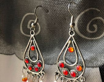 Pendant chandelier metal earrings, white beads and orange-colored Swarovski crystals.
