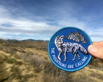 The Mountains Are Calling - round embroidered iron-on patch featuring arctic fox
