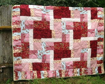 Queen size patchwork quilt made with red, robin's egg blue, green fabrics.