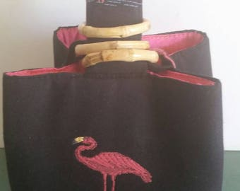 Flirty Flamingo Trio Bag is engineered to show off embroidered flamingoes front, back, bottom, and on its wrist strap.