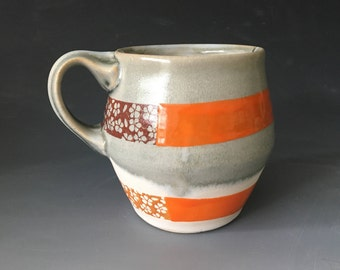 Grey and White Mug with Orange and Flower Pattern Stripes