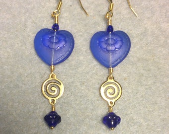 Dark blue Czech glass heart bead dangle earrings adorned with gold swirly links and dark blue Czech glass Saturn beads.