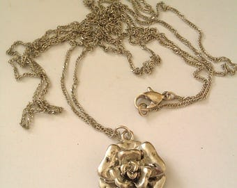 silver coloured flower pendant with long chain