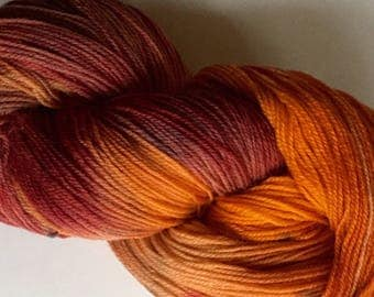 Plum pumpkin. Hand dyed yarn. Merino wool yarn, sock-fingering weight. 450 yards of autumn orange and purple.