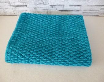 baby blanket crocheted in acrylic yarn in turquoise blue