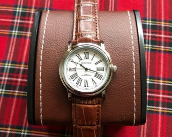 A Beautiful Men's Roman Numerals Watch With A White Face And A Leather Strap