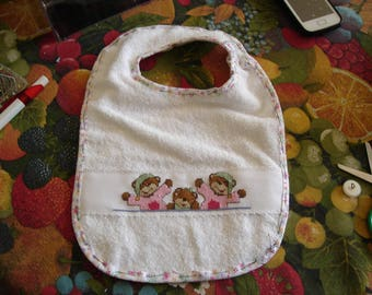 Pink bib with a teddy bear embroidered cross stitch
