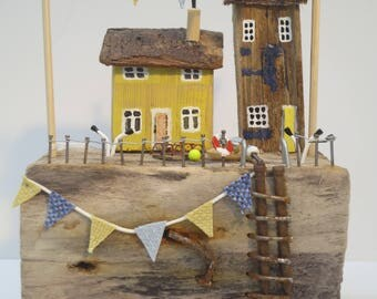Yellow and blue cottages with bunting and gulls.