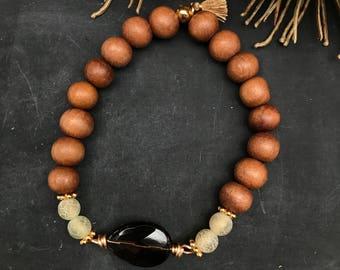 Beautiful handmade stretch bracelet made of sandalwood, gemstone crackle agate, tassel, gold-coloured beads and gemstone smoke quartz.