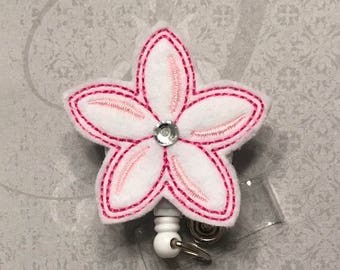 White and pink flower badge reel