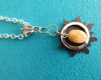 Bronze sunburst with silver encircled stone pendant.