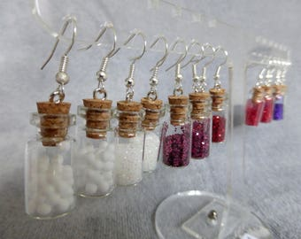 White earrings with glass vials, containing white snowballs