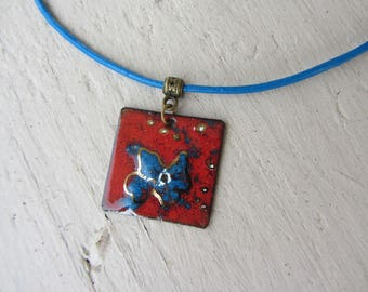 crew neck, square pendant in bright red enameled copper with bright blue and Gold Flower motif, blue leather cord