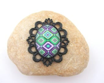 A black pendant with abstract glass cabochon