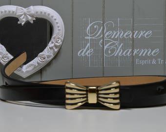 Ceinture noire avec une boucle en forme de noeud métallique coloris or