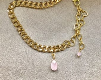gold bracelet with pink tear drop charm