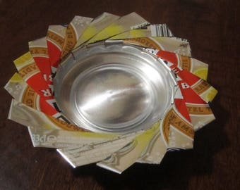 Small dish or ashtray made of recycled beer can.