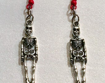 Red drop earrings with silver tone metal carved skeleton dangle charms