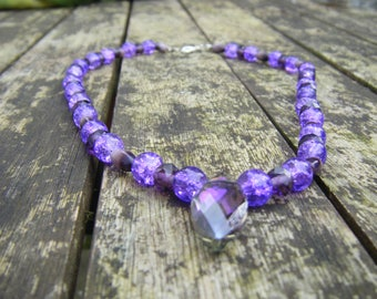 Purple crystal pendant on a beaded necklace