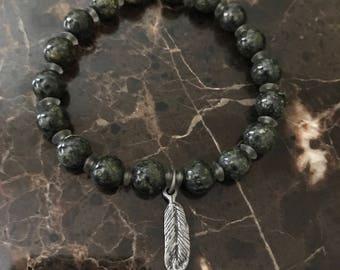 Feather charm headed stretch bracelet