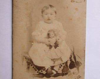 Little baby  girl posing with doll antique toy cabinet photo