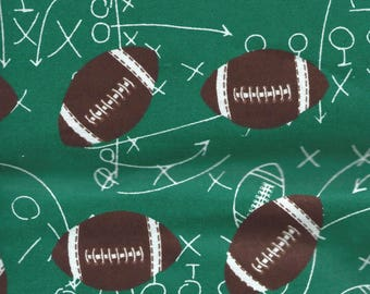 """FOOTBALLS on Green Background Flannel Fabric, 1 yard x 42"""" inches wide.  Brand new."""